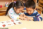 Education preschool 3 year olds boy and girl playing together with puzzle putting halves of color matching cards together