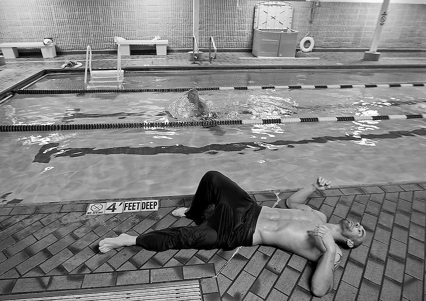 Professional MMA fighter George Sullivan collapses on the pool deck after pulling himself out of the water in an attempt to cool off after a marathon 5-hour session in the sauna.