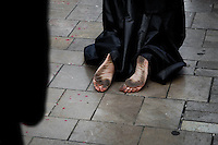 The barefoot Holy Week participant kneels on the street during the Easter procession in Malaga, Spain, 7 April 2007.