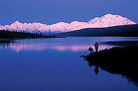 Sunset landscape of Mount McKinley and Wonder Lake with people in silhouette on the shhore. Denali National Park, Alaska.