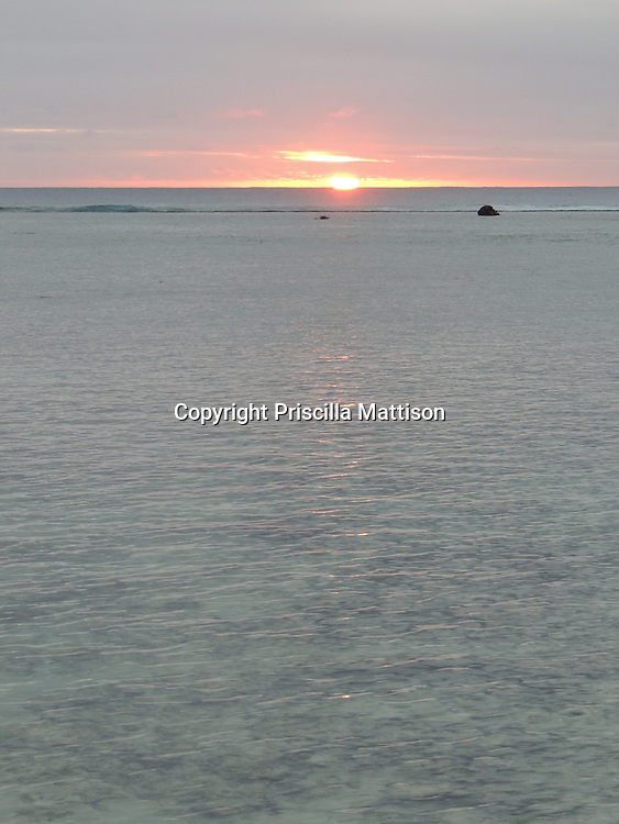 Rarotonga, Cook Islands - September 20, 2012:  The setting sun glistens on the shallow water of the lagoon.