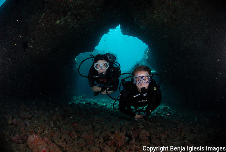 Junior divers swimming through the caves at turtle town Maui Hawaii.