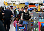 Douglas County Sheriff's Deputy Anthony Marangi shops with a student at the 15th annual Holiday with a Hero program at Walmart in Carson City, on Wednesday, Dec. 19, 2018. The program, which pairs local heroes with more than 200 K-8th graders, provides a $100 Christmas shopping spree at Walmart.  <br /> Photo by Cathleen Allison/Nevada Momentum