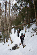 A group of hikers travel along the Lincoln Brook Trail in the Pemigewasset Wilderness of the New Hampshire White Mountains during the winter months.