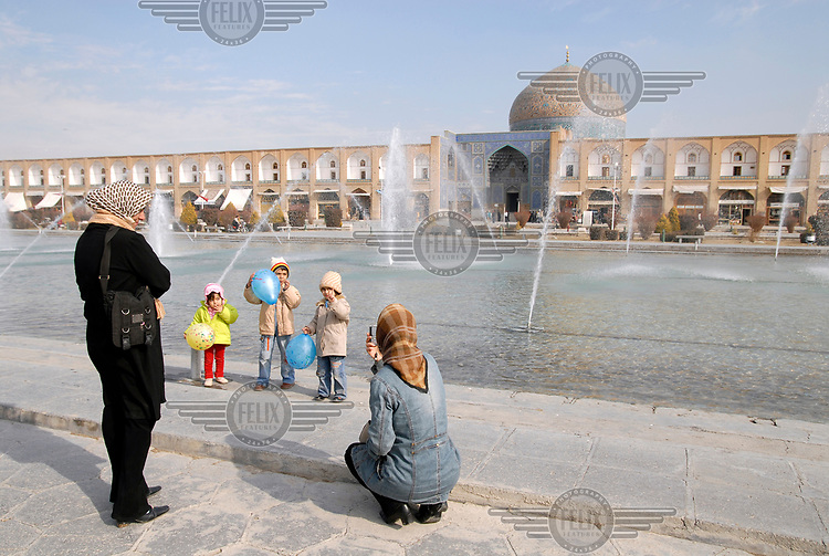 A mother photographs her children with her mobile phone on Emam Khomeini Square. The tiled dome in the back belongs to the Sheikh Lotfollah Mosque.