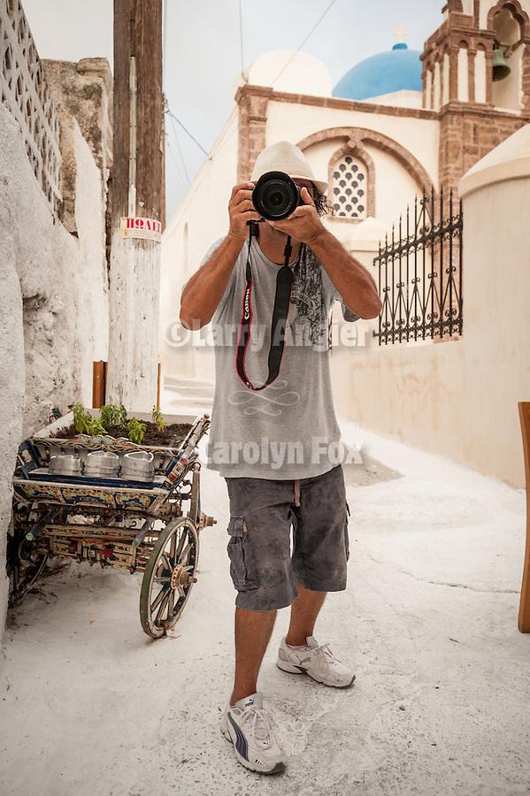 Cafe proprietor as photographer, Emporio, Santorini, Greece.