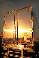 Reflection of a sunset in the back of a stainless steel truck