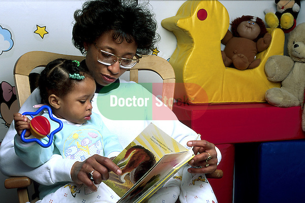 grandmother (or mother) reading book to toddler granddaughter