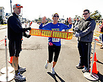 Heather Parks of Bruceton Mills, WV is the first woman to cross the finish line at the first annual Manasquan Turkey Run on Sat., Nov. 22, 2014. Holding the finish line are race director Carmen Triggiano (left) and Manasquan Borough Councilman Owen McCarthy. (Andrew Mills Digital Media)