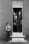 """Retired miner Charlie Hayward. He spent 49 years at South Kirkby colliery and son at front door looking straight through to the back garden. South Kirkby Colliery, Yorkshire England. Coal Miners story 1979.<br /> <br /> Charlie and his wife Lilian have never been to London, (they have only ever been on holiday to Bridlington - """"There is nowt to go abroad for. There is no where better than this country."""") let alone pottered around the Cotswolds, or peeked up a private drive in the Surrey Stockbroker Belt. Charlie was one of 16 children, he went down the pit when he was 14 years old and retired 49 years later when he was 63. He has emphysema a respiratory disease that many miners get, but it does not qualify them for any compensation.  On retirement he received £500-00 golden handshake and a certificate that is on their living room wall; for """"Long and Meritorious Service ( to the industry and """"the country"""".) Ref New Society magazine 20 Sept 1979."""