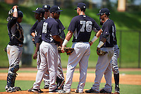 GCL Yankees 1 manager Julio Mosquera (68) pulls pitcher Anderson Severino (68) as catcher Jerry Seitz, Donny Sands, Wilkerman Garcia, Bryan Cuevas and Victor Rey (76) look on during the first game of a doubleheader against the GCL Tigers on August 5, 2015 at Tigertown in Lakeland, Florida.  GCL Tigers derated the GCL Yankees 5-2.  (Mike Janes/Four Seam Images)