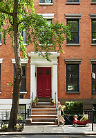 Exterior of a Manhattan town house with steps leading up to a red front door.