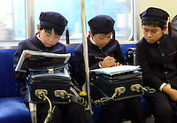 Three private school children in uniform are doing their homework together in train after school on the way back to home.