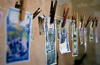 International banknotes drying on a washing line.