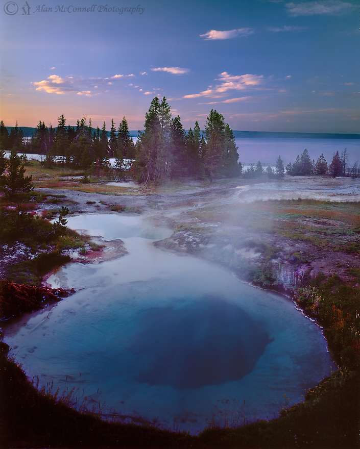 """""""The West Thumb""""<br /> West Thumb Geyser Basin, <br /> Yellowstone National Park<br />  2014<br /> <br /> An evening walk down to one of the smallest, but scenic geyser basins in Yellowstone National Park provides a tranquil time with few people.  This short walk brought me to this scene with a hot spring in the foreground and the West Thumb of Yellowstone Lake in the background.  Soon, a small herd of elk came grazing by in front of me.<br /> <br /> 4 x 5 Large Format Film"""