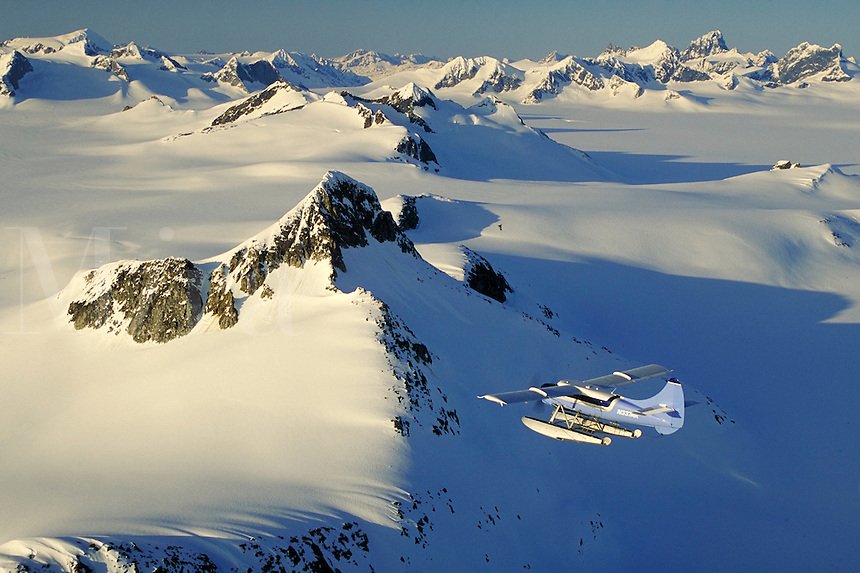 Float plane exploring mountain peaks and snow covered wilderness, Alaska, AK