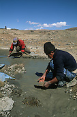 Altiplano, Peru. Poor prospectors panning for gold in a river amidst dry, barren earth.
