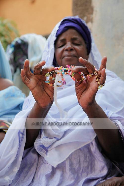 A woman shows friends a bead necklace during a baptism in Ouagadougou, Burkina Faso.