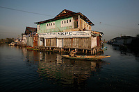 A man in canoe pass buildings on Dal Lake. Srinagar, Kashmir, India. © Fredrik Naumann/Felix Features
