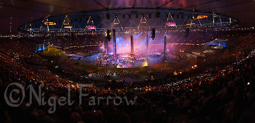 """27 JUL 2012 - LONDON, GBR - Four orange rings begin to move from the top of the stadium as workers begin to forge a fifth during the """"Pandemonium"""" section of the Opening Ceremony of the London 2012 Olympic Games in the Olympic Stadium in the Olympic Park, Stratford, London, Great Britain (PHOTO (C) 2012 NIGEL FARROW)"""