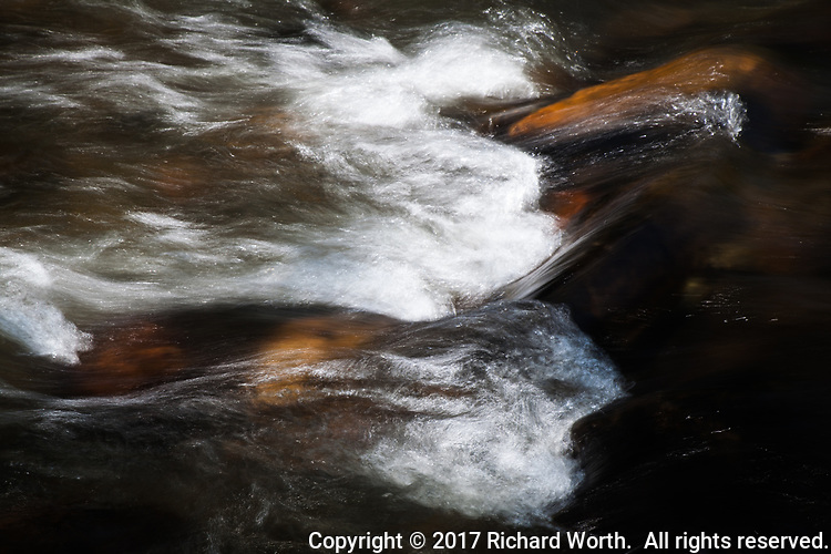 Water flowing over rocks is smoothed and softened by slow shutter speed.