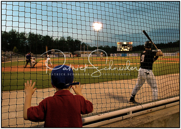 A young boy watches a Kannapolis Intimidator's game from behind the nets.