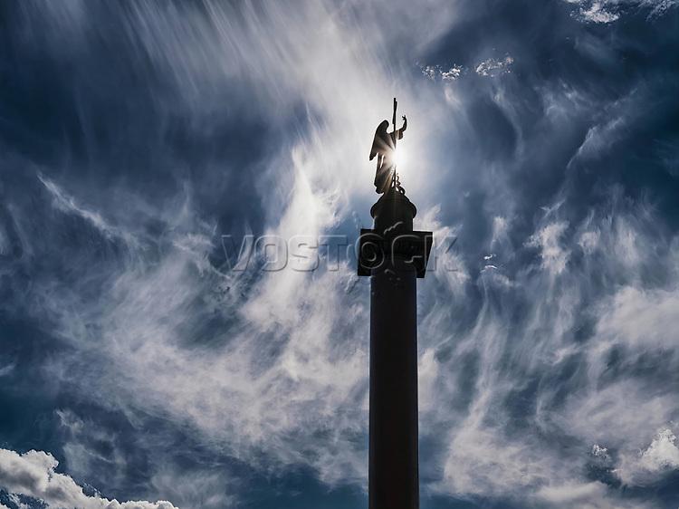 Angel black lit silhouette against dark dramatic sky and sun disk. Alexander column, Saint Petersburg, Russia.