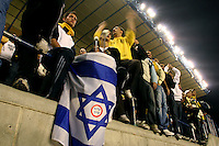 """Beitar Jerusalem soccer fans holding yellow and black flags and a national flag play drums during the match for the league against Bnei Sachnin in the Jerusalem stadium """"Tedy"""". Bnei Sachnin is the only Arab club in the Israeli Prime League, as a result of that the Betar chants are specially racist during the games between the clubs...In the center of the Israeli flag a sticker proclaiming """"Kahane was right"""", celebrating the notorious right-wing leader whose party was declared racist and outlawed by the Israeli state in 1985. Photo by Quique Kierszenbaum.."""