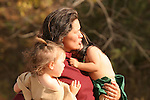 A Native American Indian mom carrying two little toddlers.   One on the left is a little girl and the little boy in green is upset.