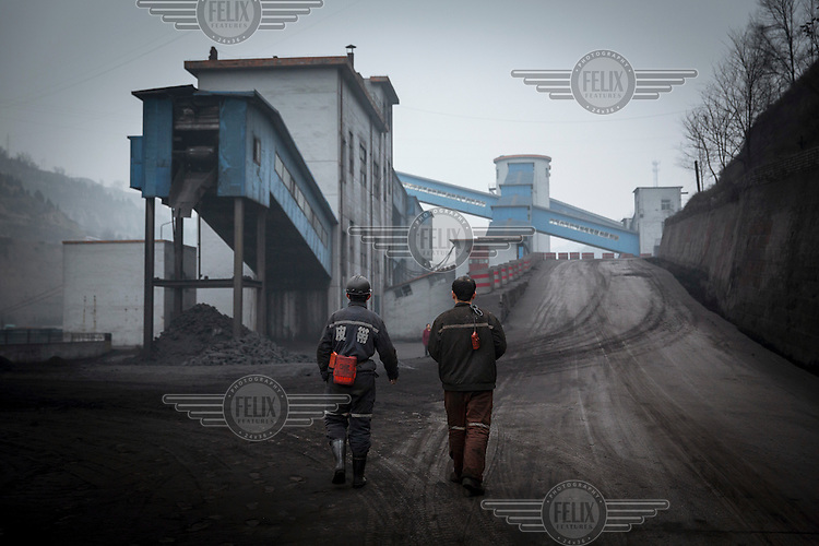 Workers, in between shifts, walk through the grounds of the Xinwu Coal Mine which is owned by Liansheng Group, a coal mining company that has been hit by the falling price of the fossil fuel leaving the firm struggling to repay its loans.