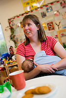 """A mother breastfeeding her young baby at a breastfeeding drop-in support group.<br /> <br /> Image from the """"We Do It In Public"""" documentary photography project collection: <br />  www.breastfeedinginpublic.co.uk<br /> <br /> Hampshire, England,UK<br /> 13/03/2013"""