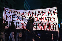 """Pictured: Protesters in helmets and armed with wooden bats holding a slogan reading """"Deep breath until the death of  capitalism and state"""" Tuesday 02 December 2014<br /> Re: At least 15 people have been arrested after a peaceful support rally for jailed hunger strike anarchist turned into violent confrontation with police. Authorities used tear gas and stun grenades to quell rioters carrying Molotov cocktails.<br /> As an estimated between 8,000 and 10,000 protesters marched through the central Athens shouting slogans in support of Nikos Romanos, the imprisoned anarchist who is staging a hunger strike as he demands the right to be able to attend university, anarchists' march got violent on the streets of Exarchia, downtown Athens."""
