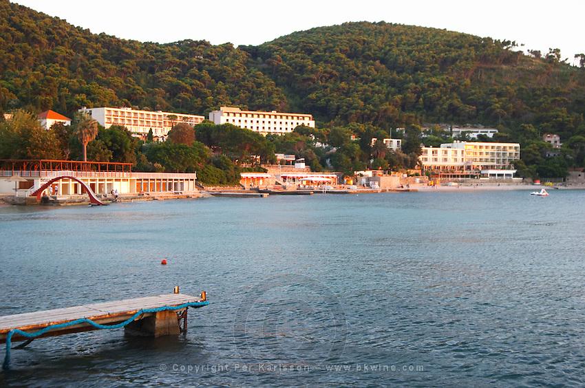 Beach, jetty and hotels in evening sunlight sunset. Uvala Sumartin bay between Babin Kuk and Lapad peninsulas. Dubrovnik, new city. Dalmatian Coast, Croatia, Europe.