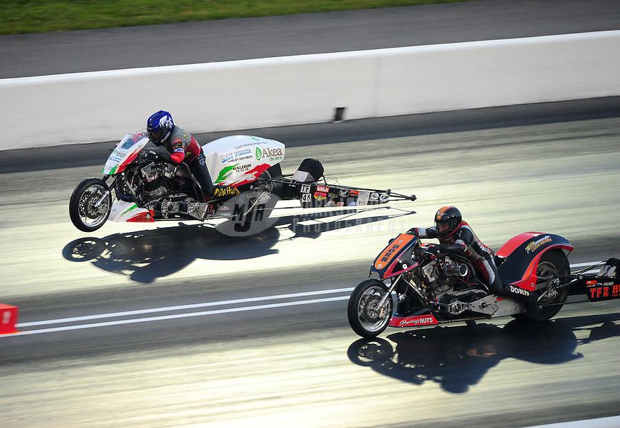 Jun. 17, 2011; Bristol, TN, USA: NHRA top fuel Harley motorcycle rider Tommy Grimes (left) races alongside Steve Dorn during qualifying for the Thunder Valley Nationals at Bristol Dragway. Mandatory Credit: Mark J. Rebilas-