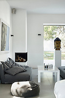 A spacious, white living room with an open fire built into one corner. The palette is simple in shades of grey
