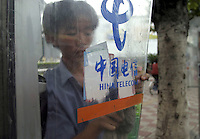 China Telecom booth in Guangzhou China. A Chinese worker peels stickers from a China Telecom phone booth in Guangzhou, China. China Telecom is a state-owned-enterprise that has a near monopoly over land-line based telecommunication services including internet services in China..