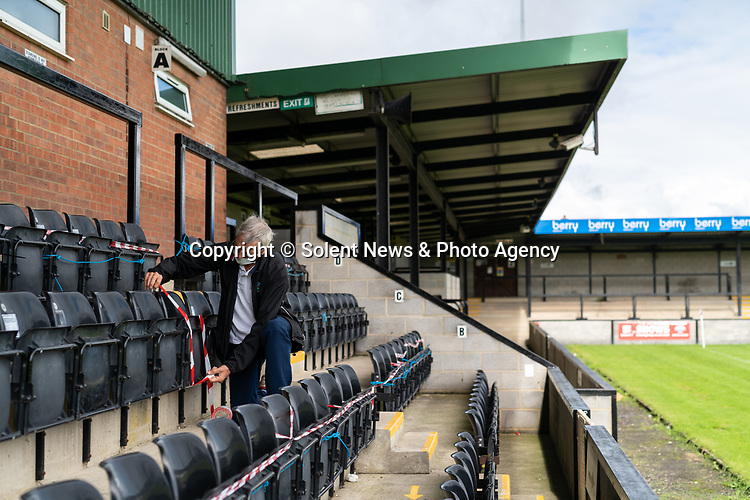 Pictured: Volunteer groundsman Peter Robinson tapes off seating to comply with social distancing measures during preparations ahead of crowds being welcomed back into sporting events at The Raymond McEnhill Stadium in Salisbury, Wilts.<br /> <br /> Inline with the governments easing of lockdown restrictions, Salisbury Football Club are preparaing to welcome back 30% of their fans as of this Monday, August 31st. <br /> <br /> Salisbury FC play in Southern League Premier Division South, or step 3 of the non-league football ladder. <br /> <br /> © Jordan Pettitt/Solent News & Photo Agency<br /> UK +44 (0) 2380 458800