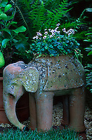Purple and white violas planted in an antique terracotta pot in the shape of an elephant
