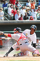 Charleston RiverDogs designated hitter Miguel Andujar #5 being called out at the plate after being tagged by Greenville Drive catcher Jake Romanski #12 during a game against the Greenville Drive at Joseph P. Riley Jr. Ballpark  on April 9, 2014 in Charleston, South Carolina. Greenville defeated Charleston 6-3. (Robert Gurganus/Four Seam Images)