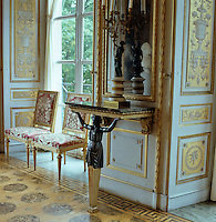 One of three console tables with a porphyry top supported by a single caryatid in black and gold in the Red Salon