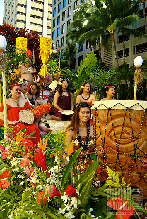 Portraying Hawaiian royalty (ali'i, alii) on a floral float in the King Kamehameha Day Parade. Downtown Honolulu. The float includes a large pahu (drum), lauhala fans and mat, yellow-feathered royal standards (kahili), kukui nut (black) leis and flo