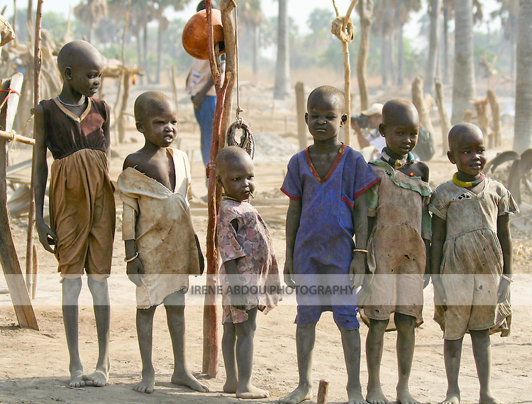 """These children are growing up in a Dinka cattle camp near Akot, South Sudan.  The Dinka are the majority ethnic group in South Sudan.  Pastoralist cattle.keepers, they traditionally live in """"cattle camps"""" of hundreds or even thousands of cows."""