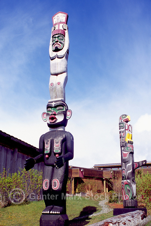 Kwakwaka'wakw (Kwakiutl) Totem Poles at U'mista Cultural Centre, Alert Bay, Cormorant Island, BC, British Columbia, Canada - Man holding Copper stands atop Dzoonokwa (Wild Woman of Woods) (left), Thunderbird sits atop Killer Whale (right)