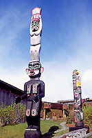 Kwakwaka'wakw (Kwakiutl) Totem Poles at U'mista Cultural Centre, Alert Bay, Cormorant Island, BC, British Columbia, Canada - Man holding Copper stands atop Dzoonokwa (Wild Woman of Woods) (left), Thunderbird sits atop Killer Whale (right)
