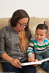 Three year old boy sitting on couch with mother reading board book, pointing, talking