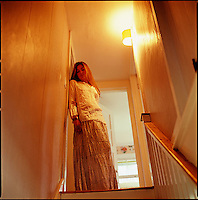 Girl, side lit by hallway light, standing at the top of the stairs<br />