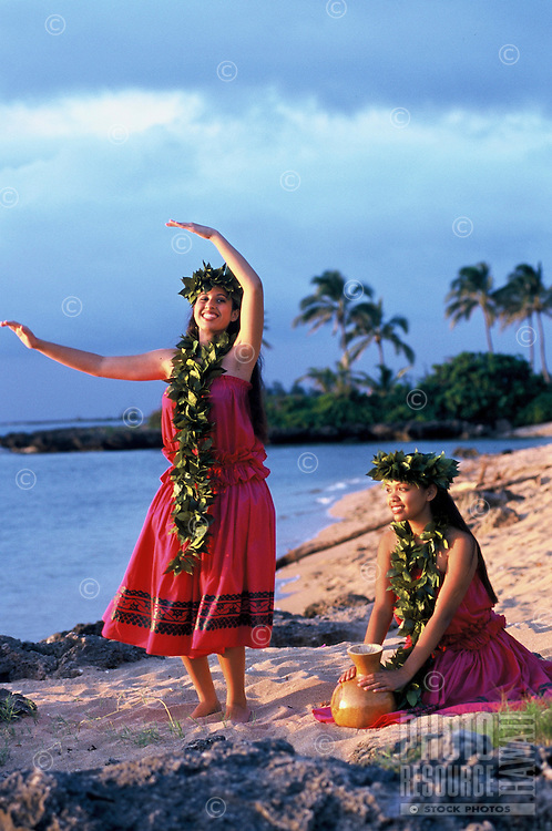 Two young women dancing kahiko (ancient) hula wearing maile leis with ipu (gourd) near ocean