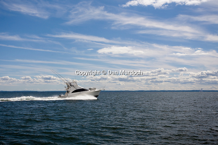 A sports fishing boat making way under a beautiful blue sky