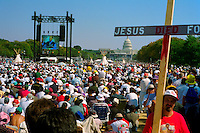 The Promise Keepers (a Christian fundamentalist organization) rally on the national mall. Crowd with video screen, man carrying large wooden cross. Washington DC USA.