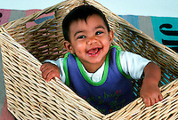 Portrait of a young, smiling baby in a basket 10 month